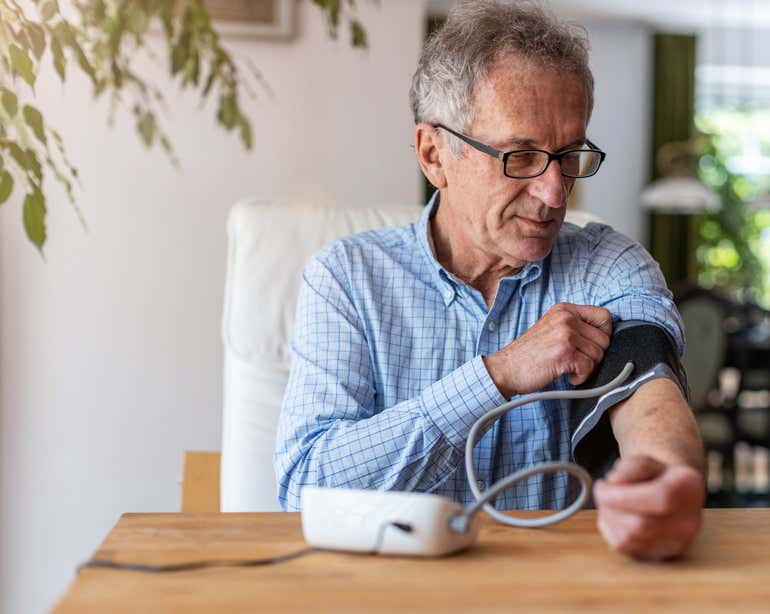 A senior man is sitting down at the kitchen table using a medical device to measure his blood pressure.