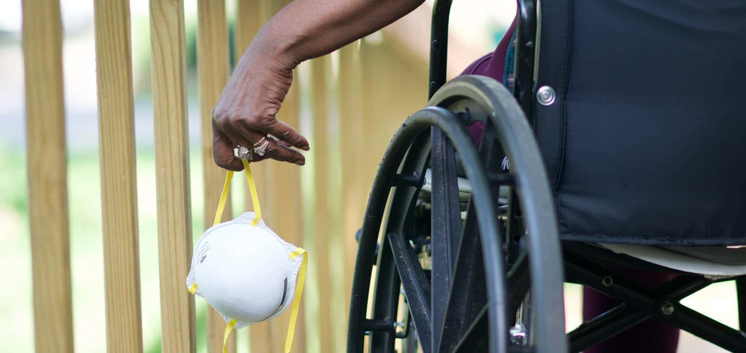 Close-up photo of an older black person in a wheelchair carrying an N95 mask.