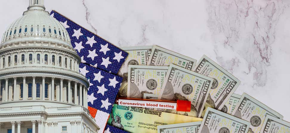 The U.S. capitol building with a backdrop of a stimulus package, American flag, U.S. dollar banknote, and coronavirus bloodtest vial.