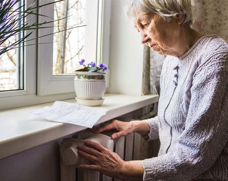 A senior Caucasian woman is seen studying her utility bill near her radiator.
