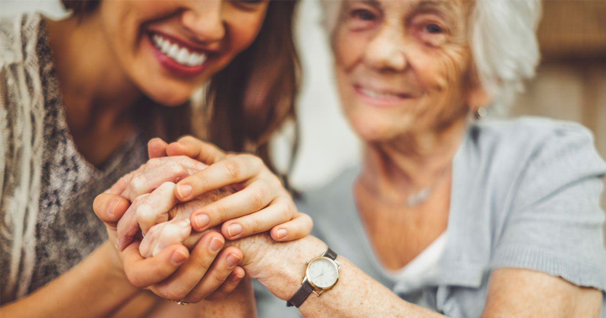 A younger female caregiver holds the hands of a senior Caucasian woman who is smiling.