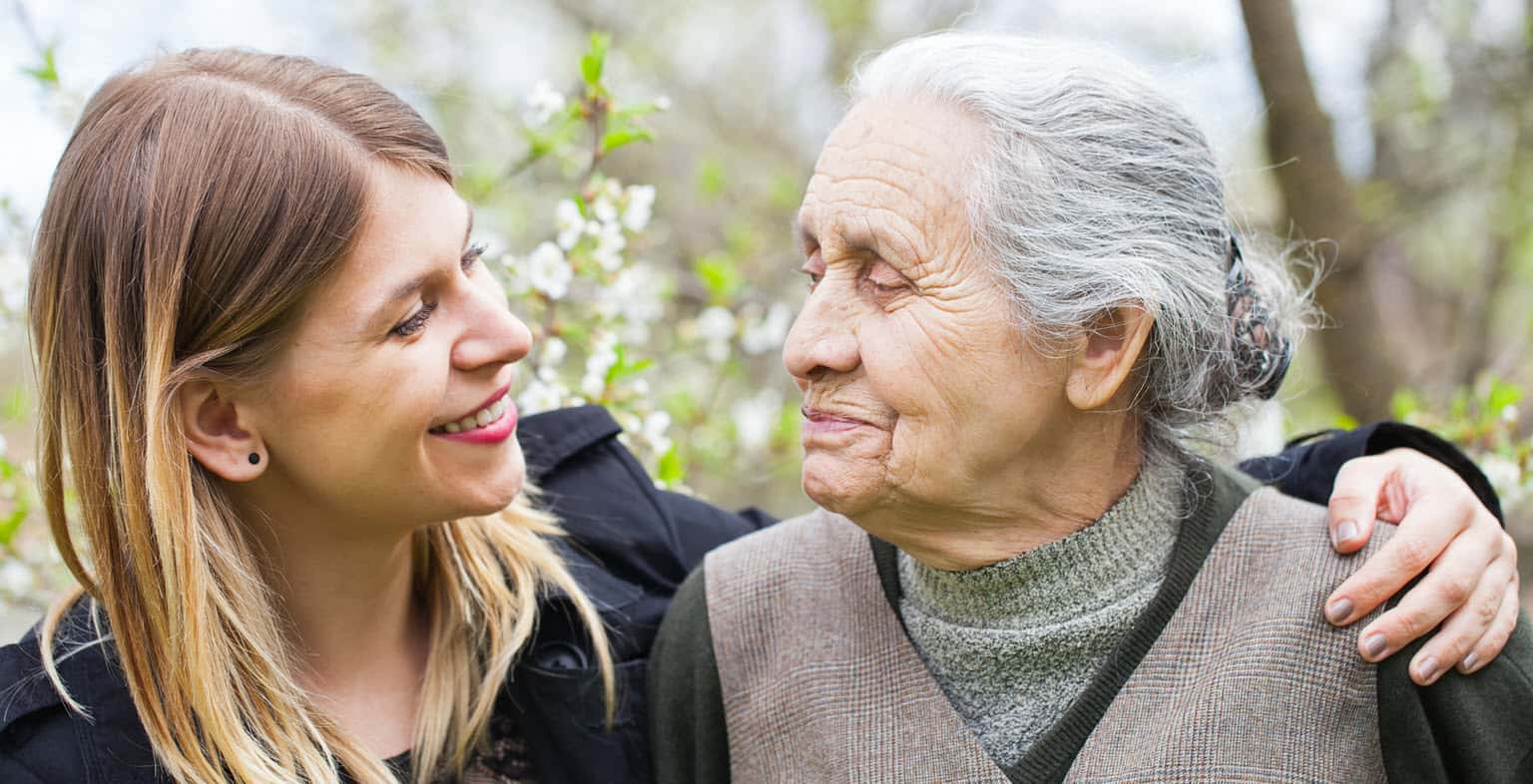 young caregiver with senior woman in park