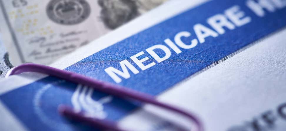 Close up shot of a Medicare card that's paper-clipped to an important healthcare document.