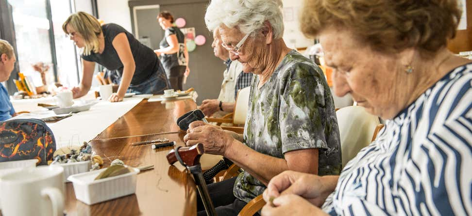 A group of female seniors are doing crafts at a local senior center.