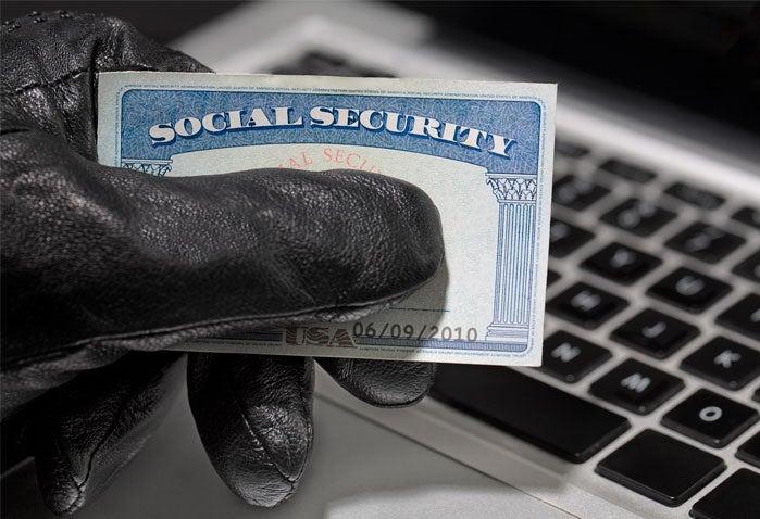 Un estafador con guantes negros tiene una tarjeta de seguridad social sobre un teclado.