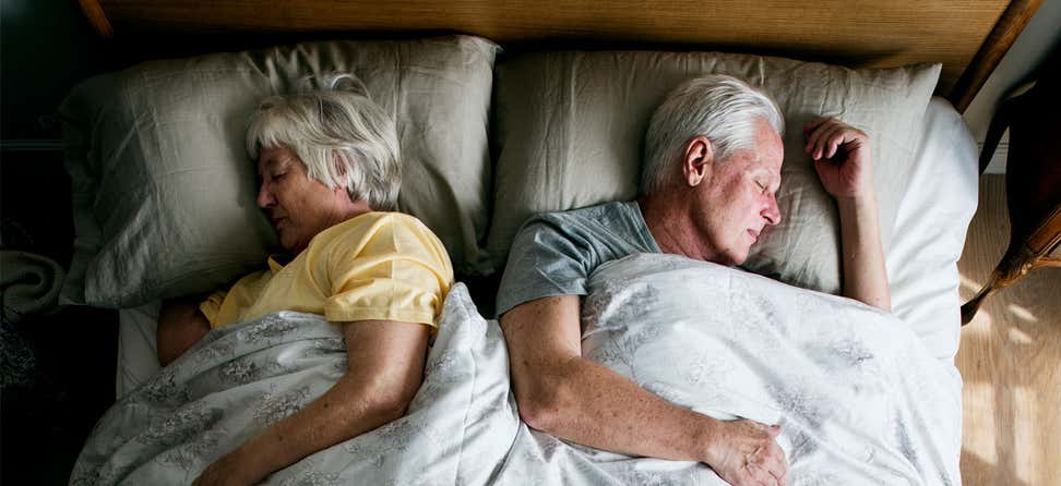 A senior Caucasian couple is sleeping comfortably in bed together.