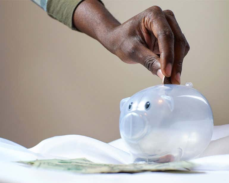 A Black senior hand is placing coins in a clear piggy bank.