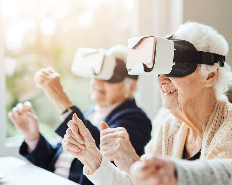 Two senior women are at a senior center, using virtual reality goggles during a group activity.