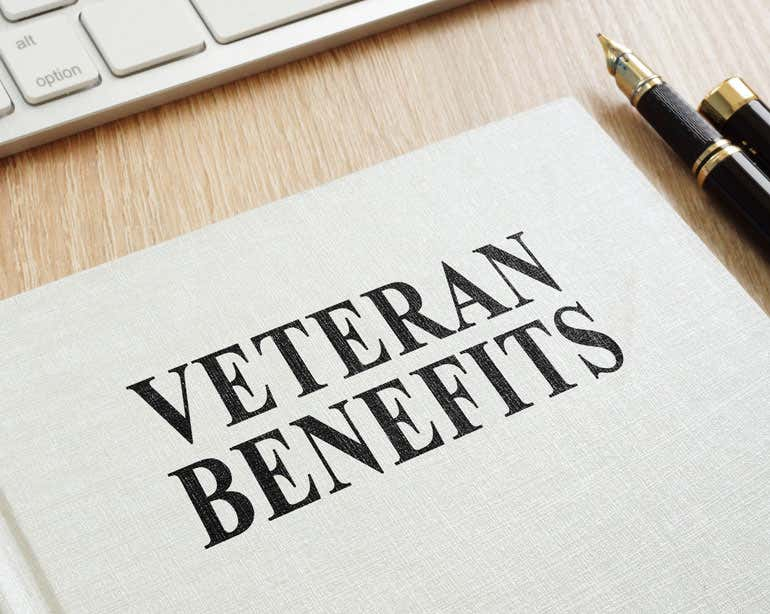 "A book on a desk reads ""VETERANS BENEFITS"" in all caps."
