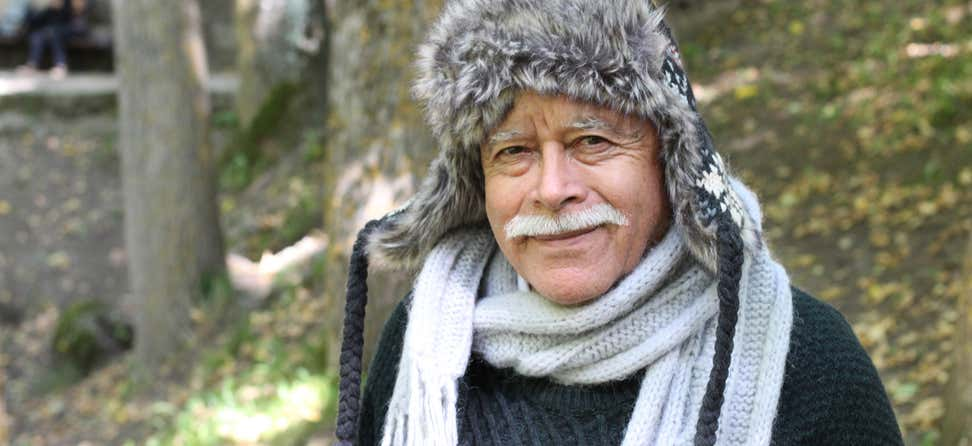 A senior eskimo man, wearing a warm hat and scarf, is looking at the camera smiling.