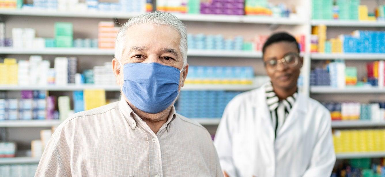 Un anciano está en la fila de la farmacia esperando para recoger su receta.