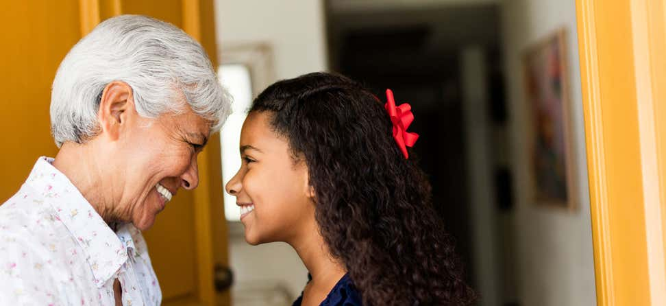 An older woman is looking into the eyes of her granddaughter, both are smiling at each other.