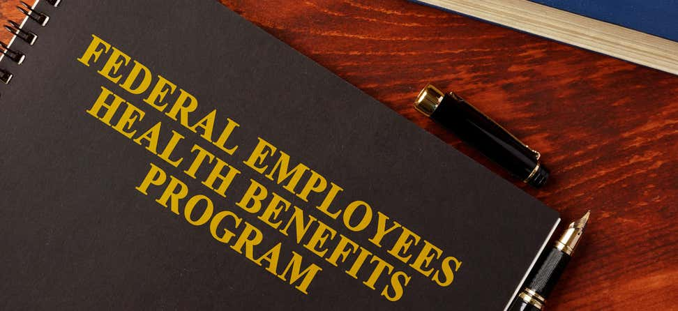 """A close up shot of a handbook with the words """"Federal Employees Health Benefits Program"""" on the face."""