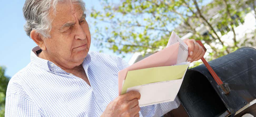 Older Hispanic man getting mail out of his mailbox outside.