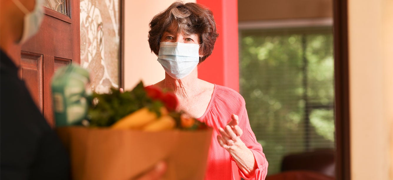 A senior masked woman stands at the door of her house receiving a grocery delivery.