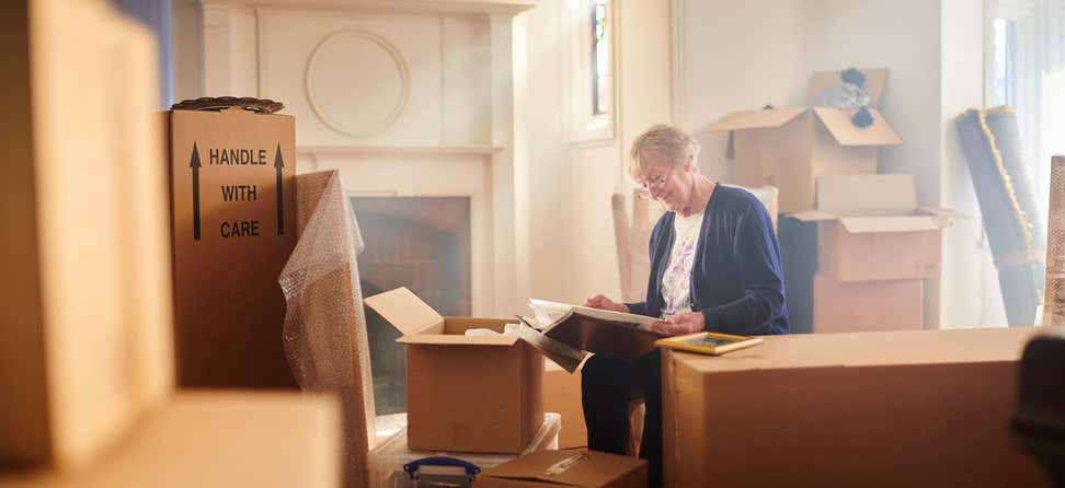 A senior woman is sitting in her house, full of boxes that are packed - looking at a photo album and remembering the past.