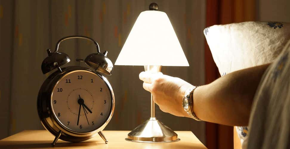 Person reaching to turn off lamp next on bedside table