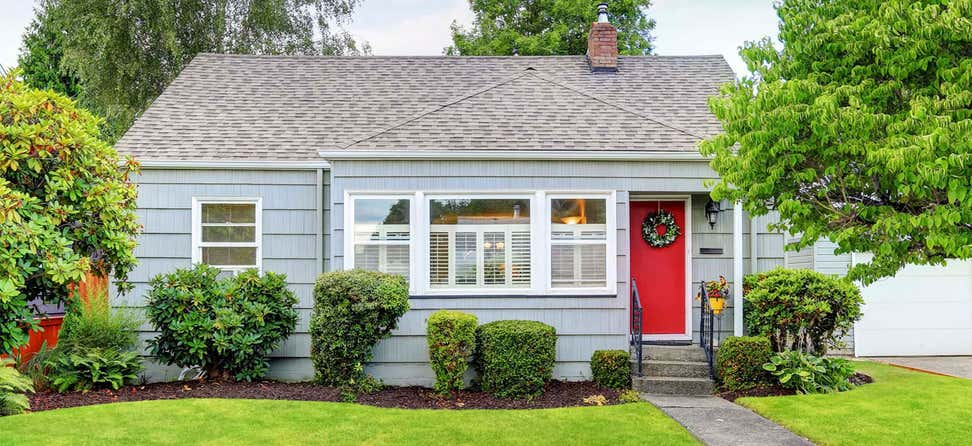 A picturesque street view of a cozy bungalow home with blue paint and a red door.