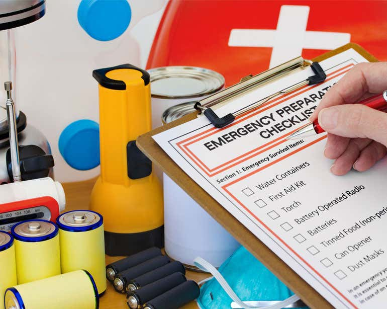 A up close shot of an emergency preparedness checklist along with the items on the list, like batteries and others.