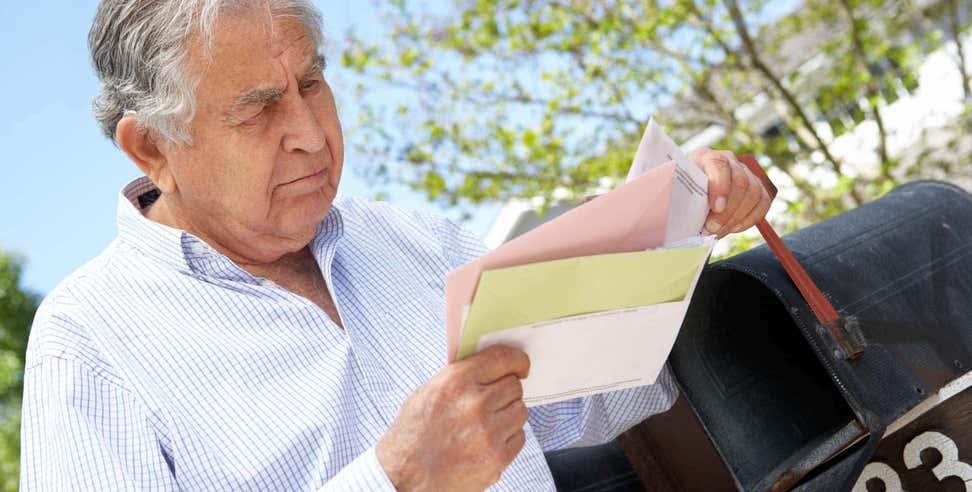 Older man checking letter at mailbox.