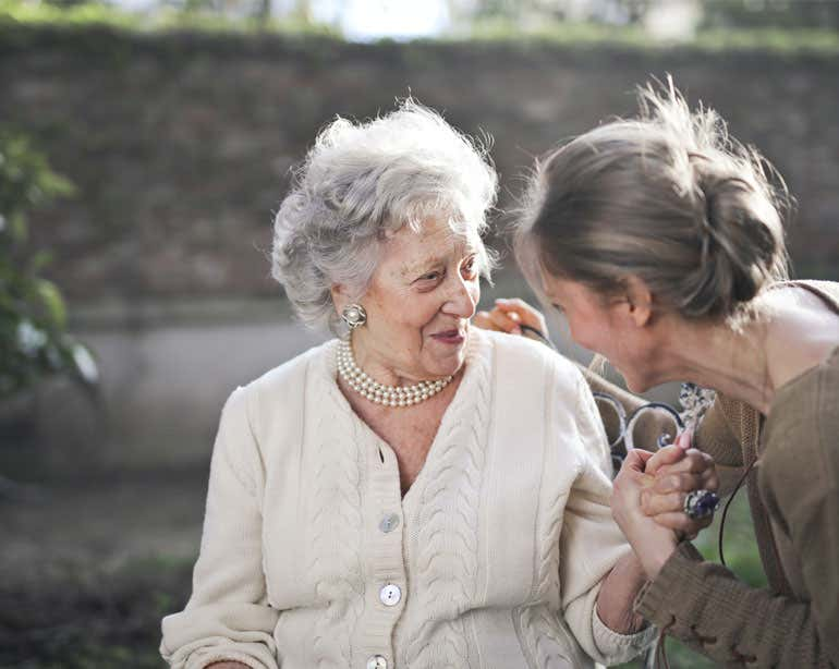 An older female caregiver is seen holding the hand of a Caucasian senior woman. Both are smiling.