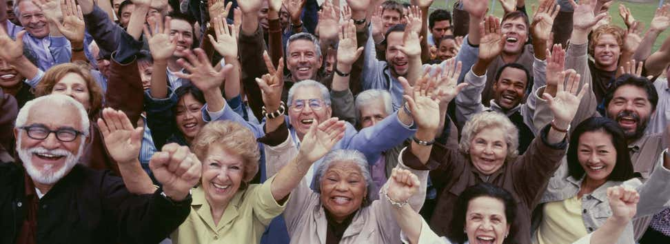 A large group of older adults, all multi-ethnic, have their arms raised and are cheering with joy.