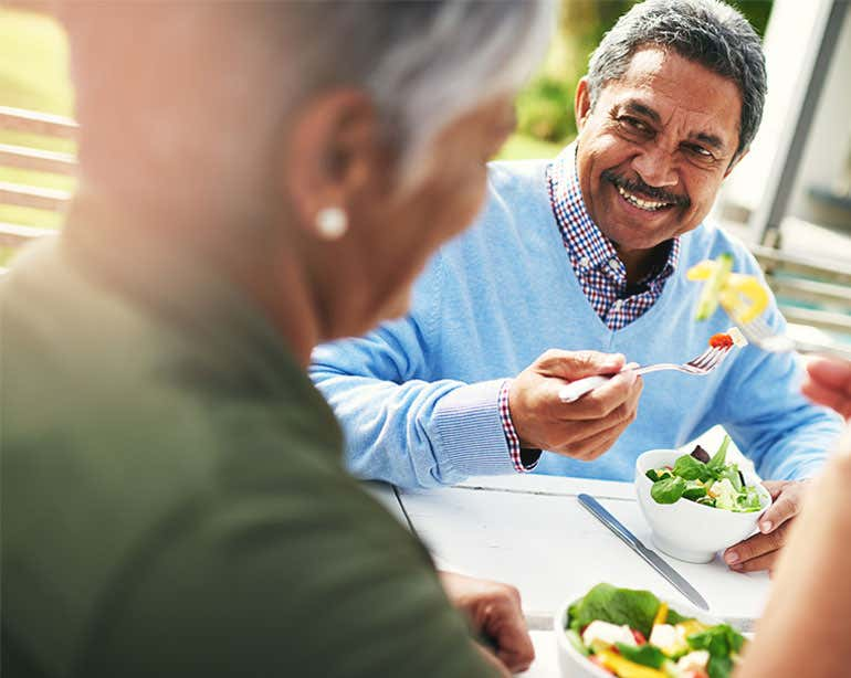 A senior Black man is enjoying a salad with his wife at lunchtime.