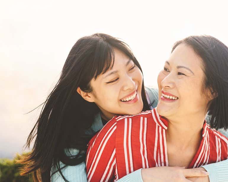 A young female Asian caregiver is embracing her senior mom outside, both are laughing.