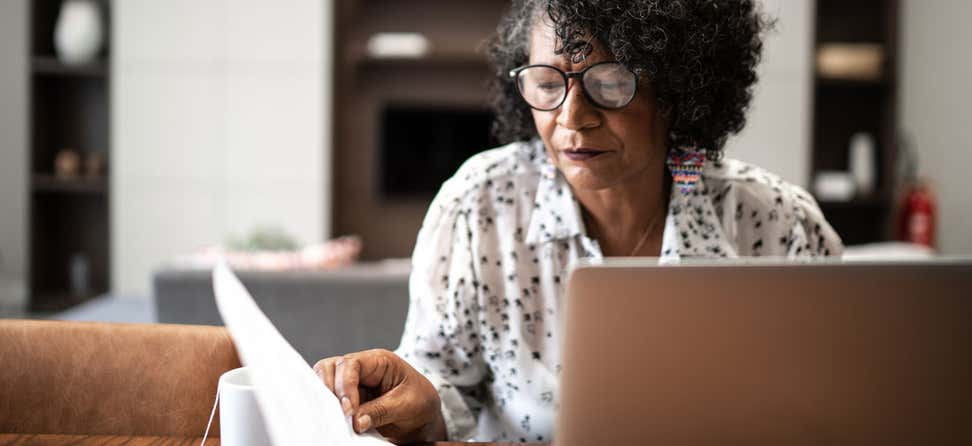 A Black senior woman is at her kitchen table, looking at her financials and working on her laptop.