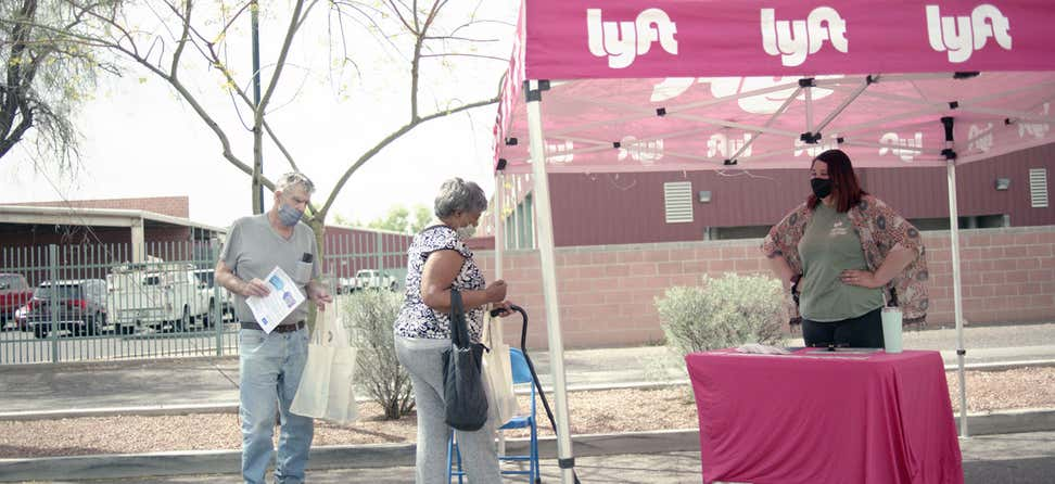 A senior Black woman gets dropped off at a Lyft tent during a COVID-19 vaccine event in Arizona.
