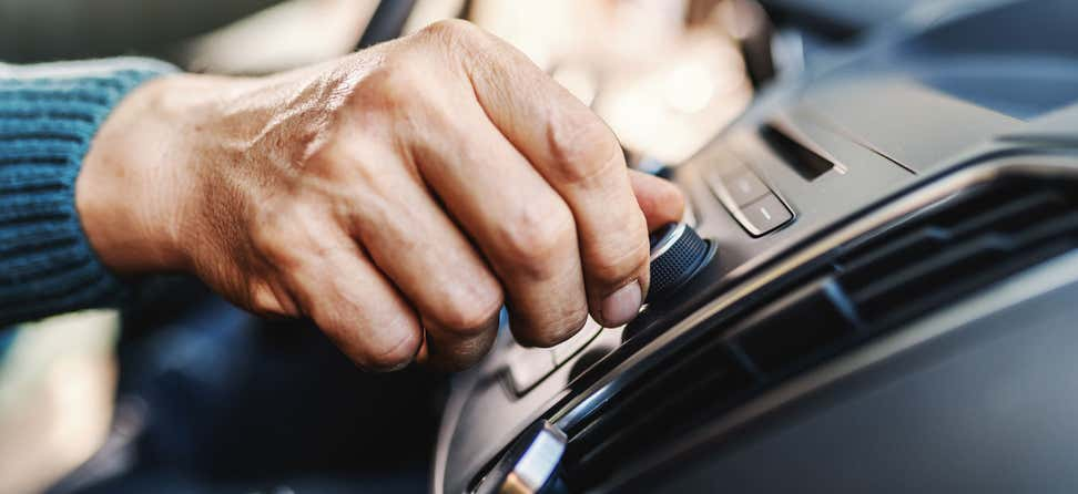 A close-up shot of a hand that's turning the dial of a car radio, hoping to find the perfect station.
