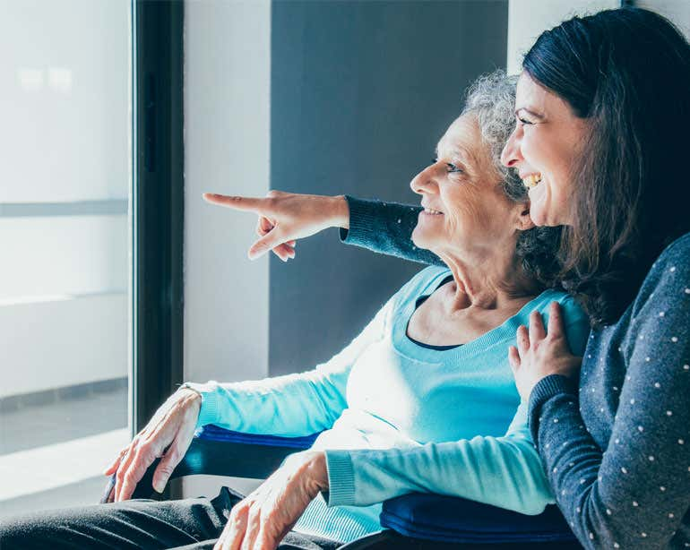 An older female caregiver has her arms around her senior female loved one as they both stare happily outside.