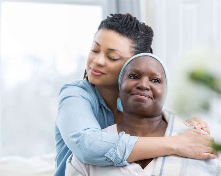A younger Black female hugs her grandmother in a warm embrace.