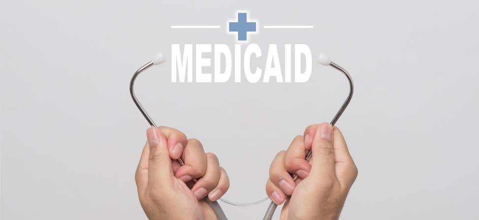 """A stethoscope is pictured, opened, with the words """"Medicaid"""" in between."""