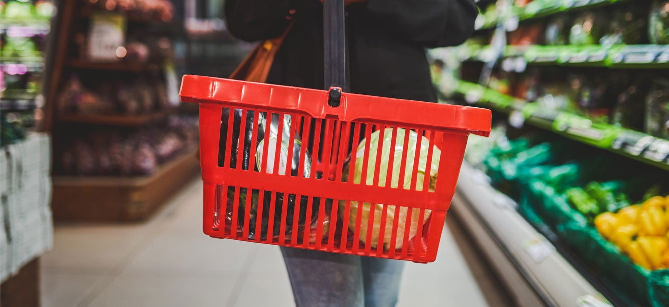 A female is holding a red grocery basket with produce in it in a aisle at the grocery store.