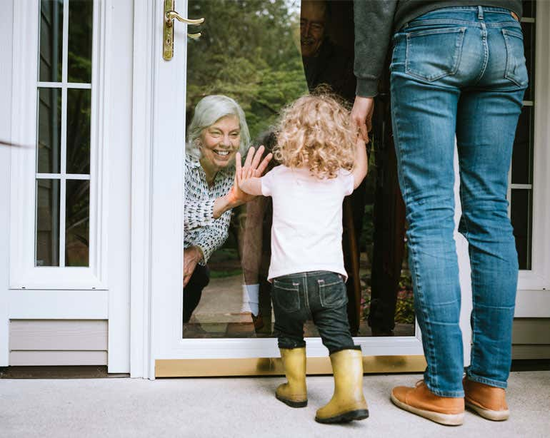 A grandmother is waving to her granddaughter and daughter through a sliding glass window, being careful to practice social distancing during the pandemic.