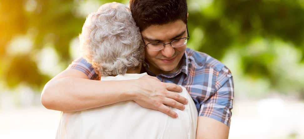 Younger male wearing glasses is hugging a senior woman.