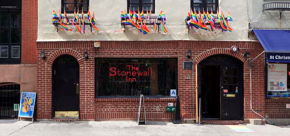 The Stonewall Inn with Pride flags waving.