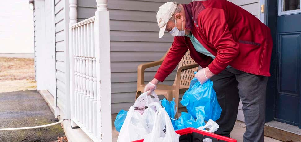 Senior man wearing a protective mask and gloves is taking groceries out of the bins left on his porch into his house during COVID-19 pandemic outbreak.