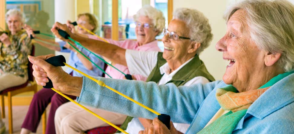 A group of seniors are doing stretch band exercises together at a senior center.