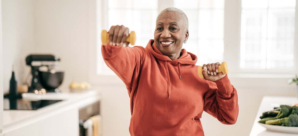 A senior Black woman is exercising with dumbbells at home.