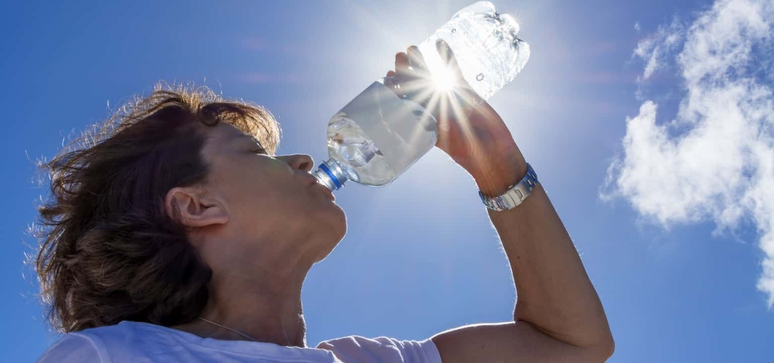 Woman, senior, drinking water in the sunlight, back lit image with sunbeams
