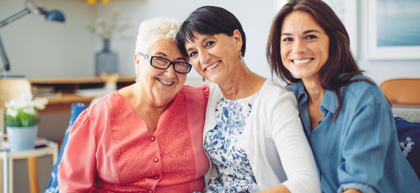 A group of intergenerational women are sitting on the couch, smiling and posing for the camera.