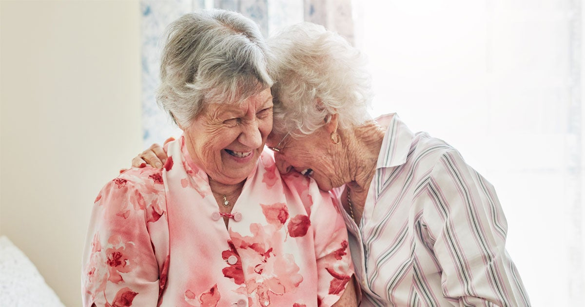 Two Caucasian senior female friends are laughing and hugging, sharing a joke together.