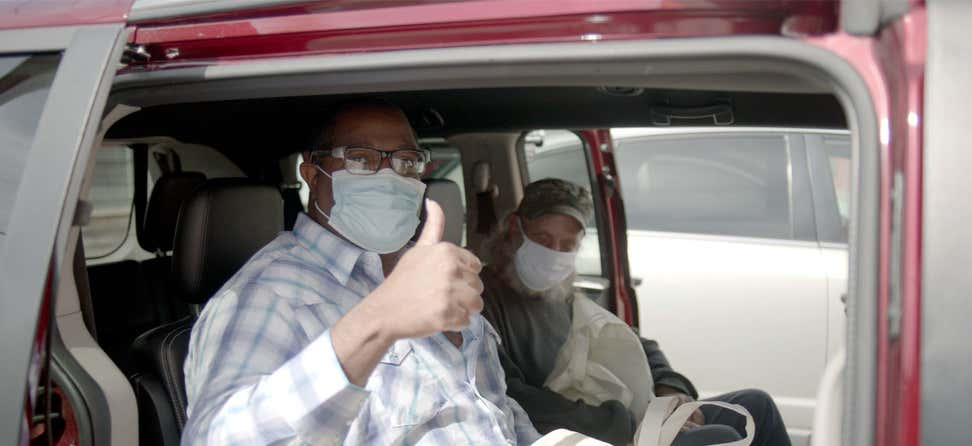 Two senior men are waiting in their Lyft ride after getting their COVID-19 vaccine at an event in Arizona.