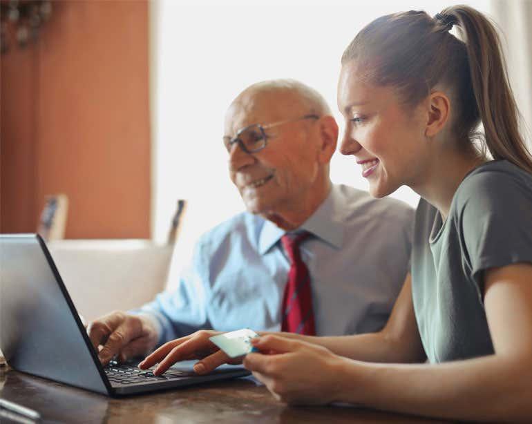 A younger benefits enrollment professional helps a senior find benefits options online.