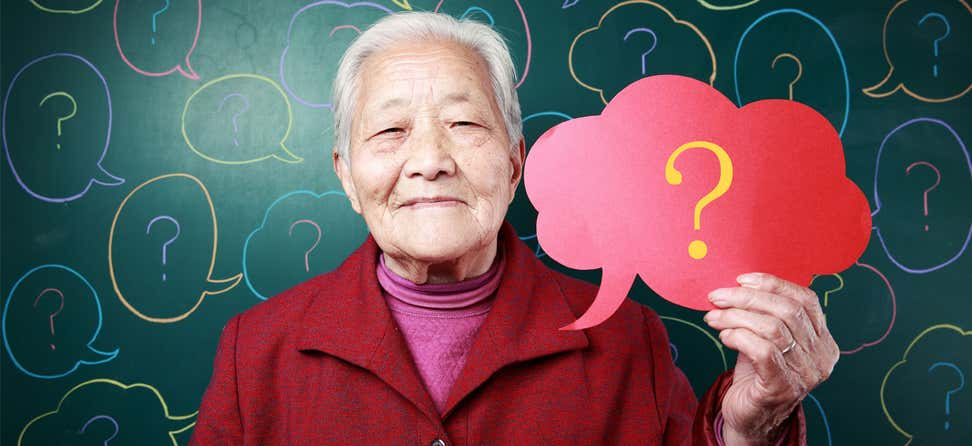 An older Asian woman is holding a red thought bubble sign in her hand that has a yellow question mark inside of it.