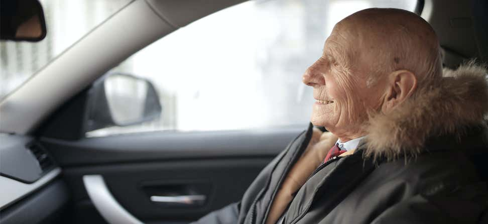 A senior male is riding in a Lyft, smiling on his way to his destination.