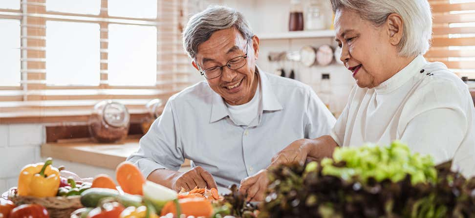 A senior Asian couple in the kitchen is cooking with fresh produce.
