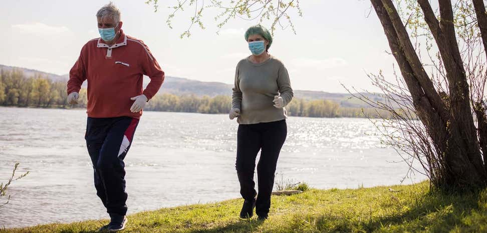 senior couple wearing masks during COVID pandemic goes for a jog by the river